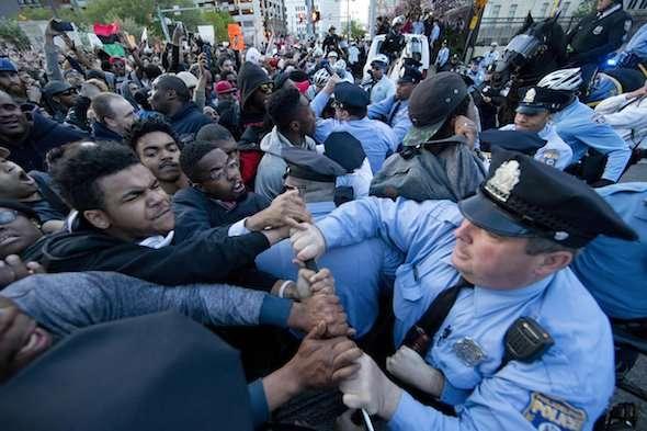 Des protestataires se heurtent un cordon de police après un rassemblement devant la mairie de Philadelphie jeudi. L'action faisait suite aux journées d'émeutes à Baltimore, après la mort de Freddy Gray. (AP / Matt Rourke)