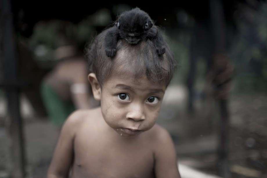 Awá-guajá, un niño del pueblo Awá con una cría de mono aullador negro, Brasil. (Imagen de Survival)