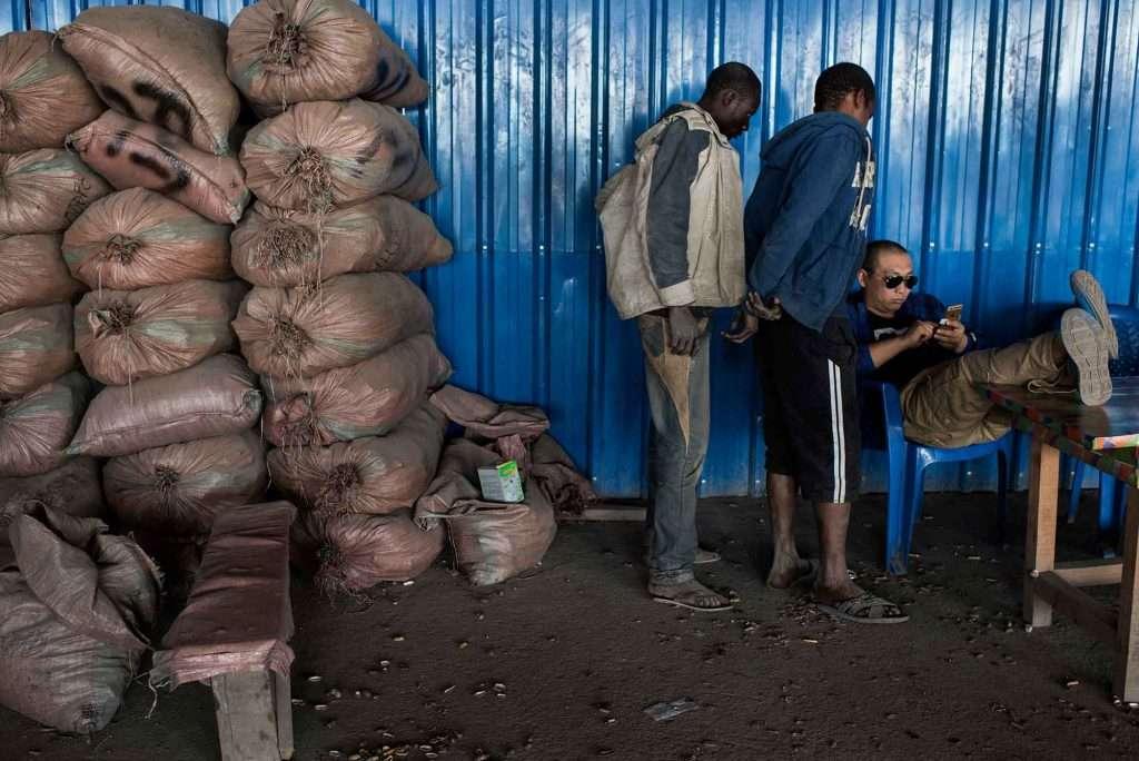 """KOLWEZI, REPUBLIQUE DEMOCRATIQUE DU CONGO – 7 JUIN. Un """"comptoir"""" chinois, ou compteur, assis, calcul un paiement tandis que des """"creuseurs"""", ou mineurs, observent attentivement, à Musompo, un marché de minerais, près de Kolwezi, le 7 juin 2016."""